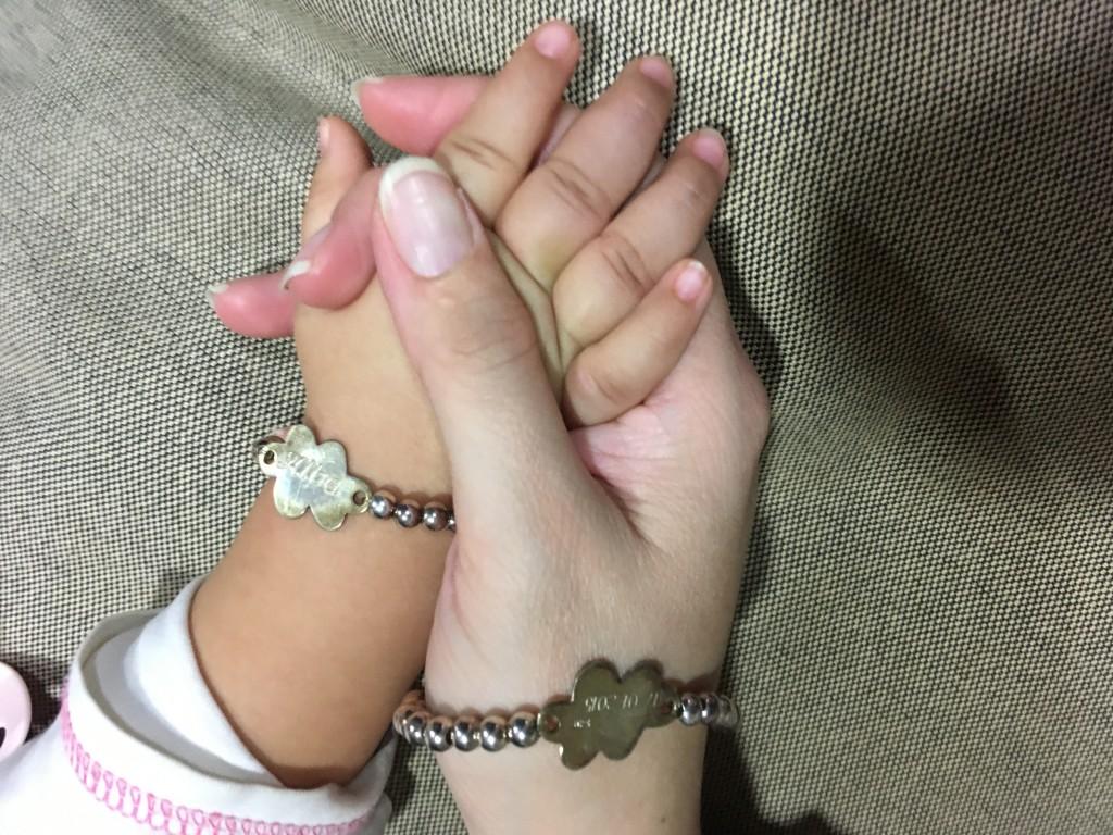 Las manos de Noe y Alba con sus pulseras nube