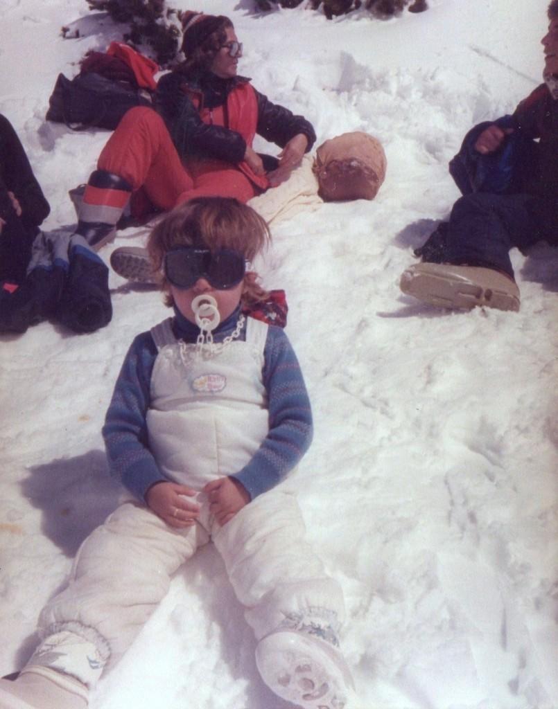 Mami de pequeña sentada en la nieve con chupete