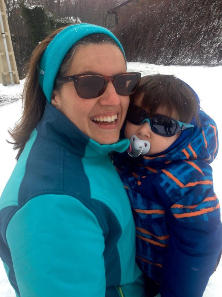 Mami arrodillada en la nieve con Vikingo encima en brazos