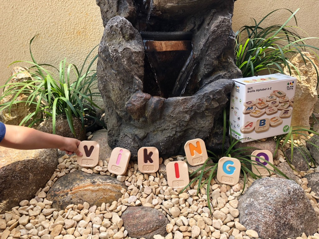 En la fuente de nuevo, entre las piedrecitas y las plantas se ve la caja del juguete, las letras formando la palabra vikingo y la mano del Vikingo sujetando la V.