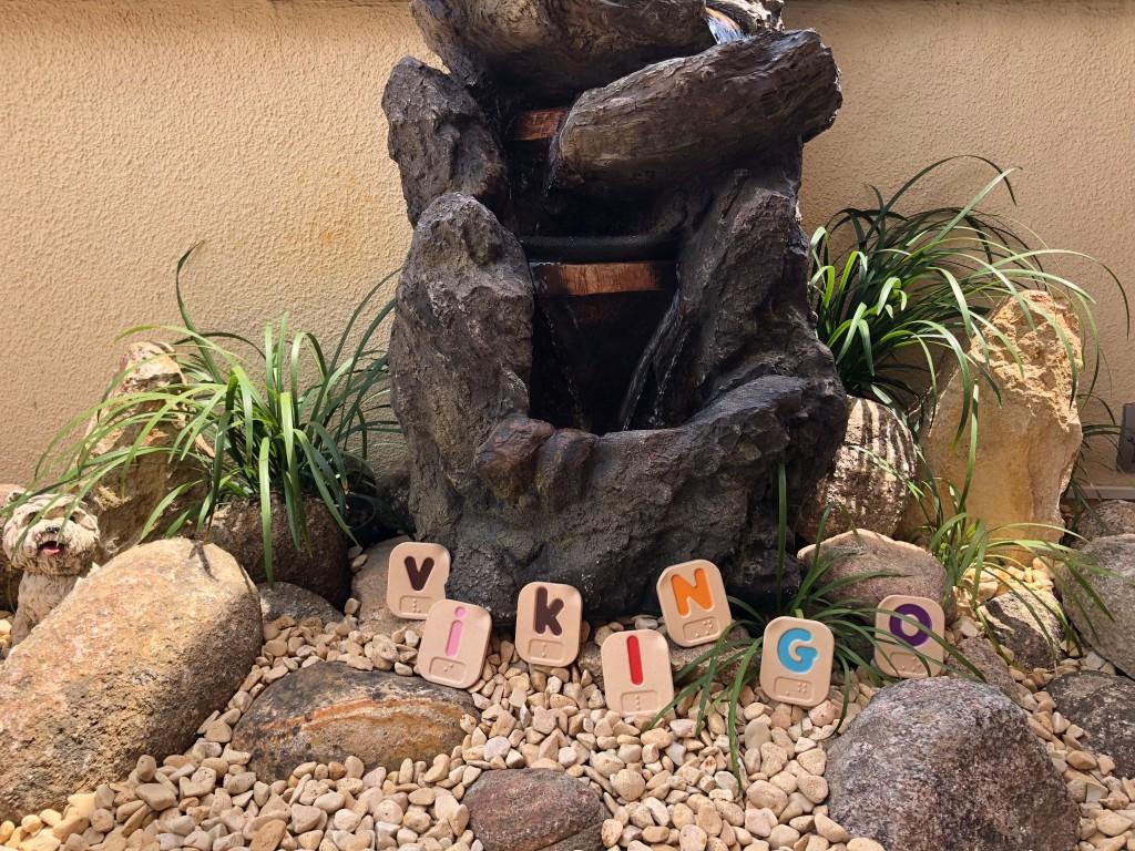 Entre las piedrecitas y plantas de una fuente, están colocadas las letras que forman la palabra VIKINGO