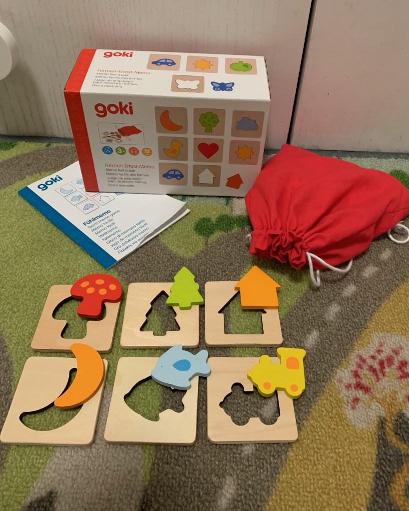 La caja y la bolsa del memory de formas y se ven 6 parejas formadas: Seta, árbol, casa, luna, pez y tren.