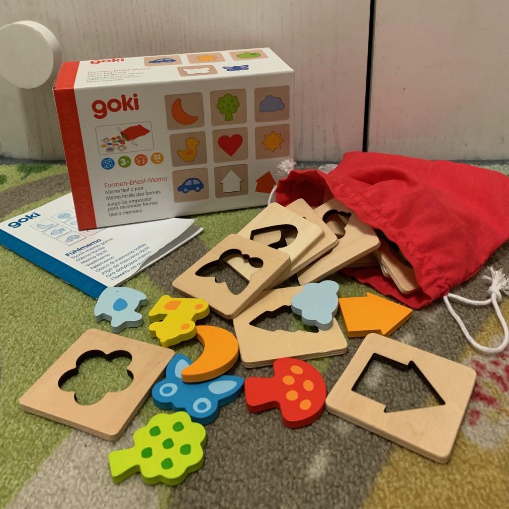 Memory de formas. Se ve la caja, las instrucciones, la bolsa de tela y las piezas saliendo de ella.
