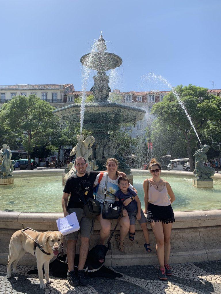 Juanjo, Núria, el peque y sus perros guía en la Praça du Rossio en Lisboa junto a una fuente con varias esculturas.