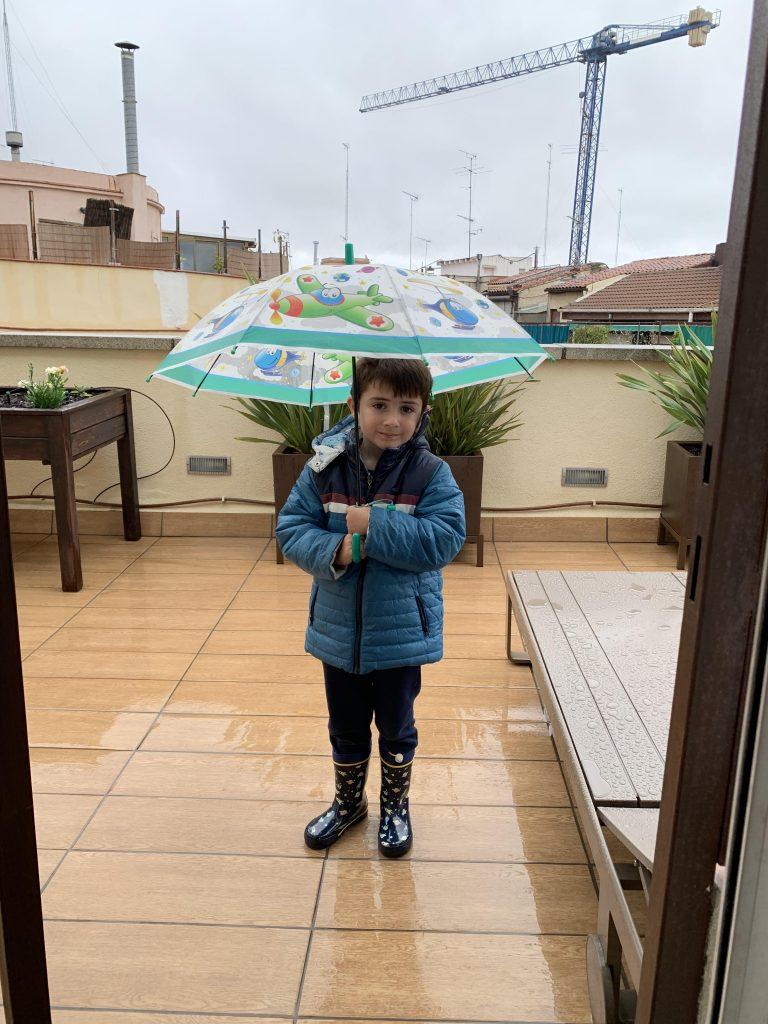 Podcast de confinamiento. El pequeño Vikingo en la terraza con botas, anorak y paraguas en un día lluvioso.